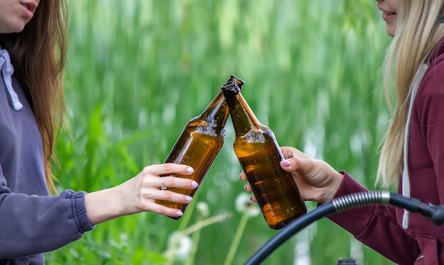 자연 속에서 맥주병을 들고 있는 남자의 손. 강가에서 휴식을 취하십시오. 자연. 선택적 초점