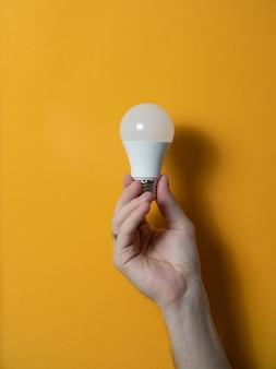 革新と創造的なコンセプトのための電球を握る男の手。