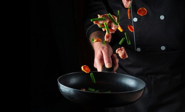 전문 요리사의 손이 검은 배경에 프라이팬에 야채와 쇠고기 고기 조각을 던졌습니다. 레스토랑 요리 개념입니다. 무료 광고 공간