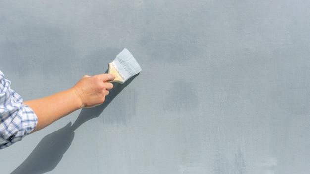 Рука мастера с кистью красит стену в синий цвет.