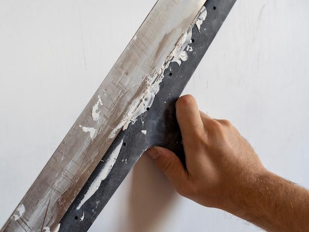 벽에 작용하는 긴 주걱으로 일하는 작업자의 손. 인테리어 작업, 건설 개념