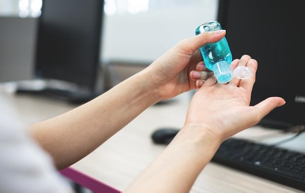 コロナウイルスの衛生状態を防ぐために手の消毒剤ボトルを持っている若い女性の手。