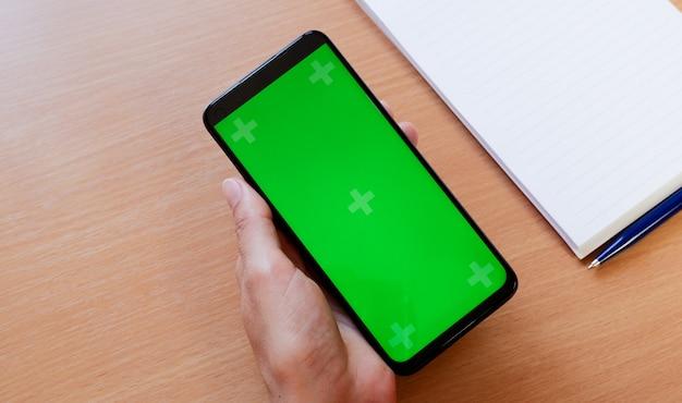 ノートブックを持ってテーブルに緑色の画面で電話を持っている若い女性の手。