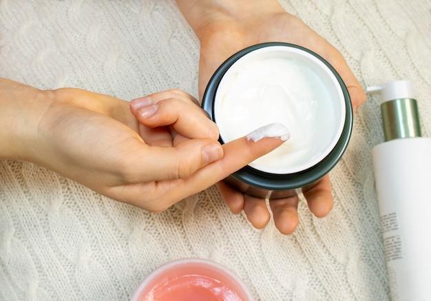 若い女性の手が瓶からフェイスクリームを取ります。スキンケア、水分補給、栄養。
