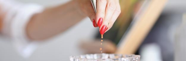 매니큐어를 한 예술가의 손이 물 한 잔에서 브러시를 꺼내는 가정 교육