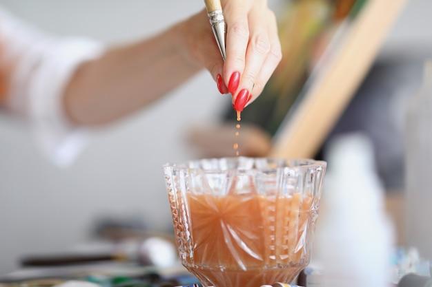 Рука художника с маникюром вытаскивает кисть из стакана воды домашнее обучение