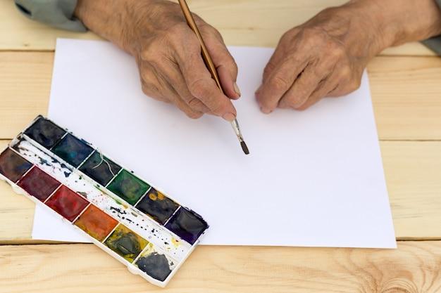 Рука пожилого мужчины держит кисть для акварели. концепция активной и счастливой старости, творчества в зрелом возрасте, новых начинаний. изображение.