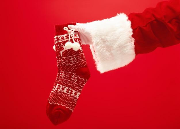 Рука санта-клауса, держащая рождественские вязаные носки на красном