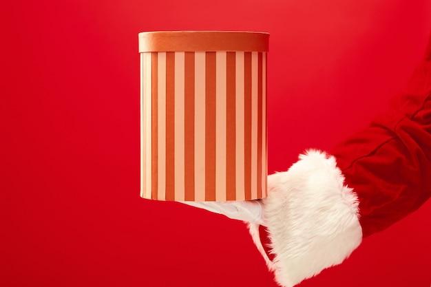 赤の背景に贈り物を持ってサンタクロースの手。季節、冬、休日、お祝い、ギフトのコンセプト