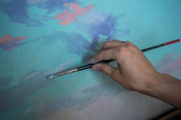 Рука художника, написавшего холст масляной краской