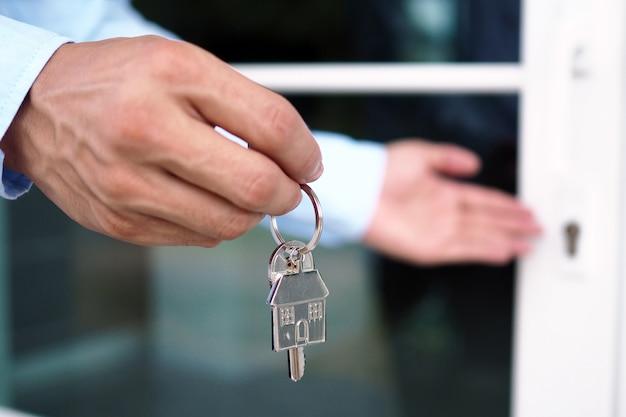 銀行家の手が家の鍵を握っています。住宅ローンと住宅ローンのコンセプト