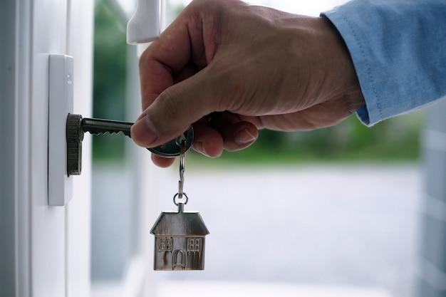 Рука банкира держит ключ от дома. концепция ипотеки дома и земли