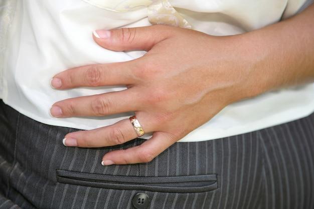 신부의 손이 신랑의 허리를 껴안았다. 사랑에 빠진 부부의 관계