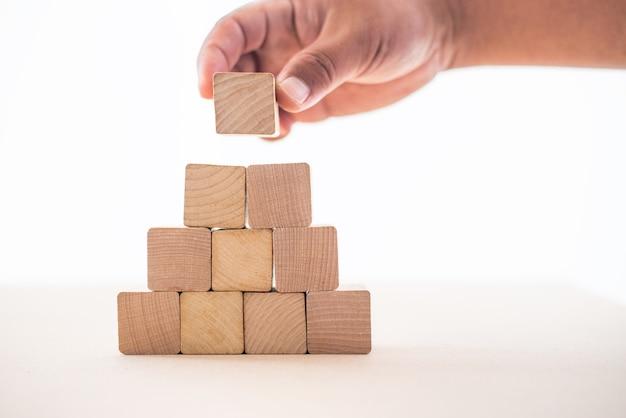 ビジネスマンの手は、ビジネスの安定性を示すために、白い背景に置かれた木製のブロックを家として捉えました。