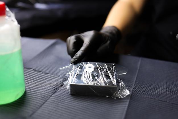 Рука мастера перманентного макияжа пальцами держит колпачок с пигментом.