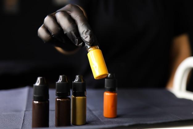 指でタトゥー用の黄色い顔料を上げるアートメイクの達人の手