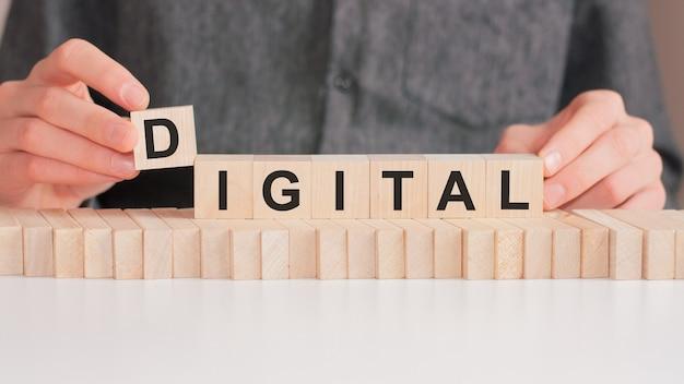 손은 digital이라는 단어에서 문자 d가있는 나무 큐브를 놓습니다. 단어는 테이블의 흰색 표면에 서있는 나무 큐브에 기록됩니다.