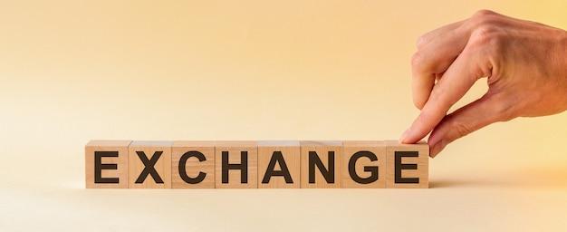 손은 exchange라는 단어에서 문자 e가있는 나무 큐브를 넣습니다.
