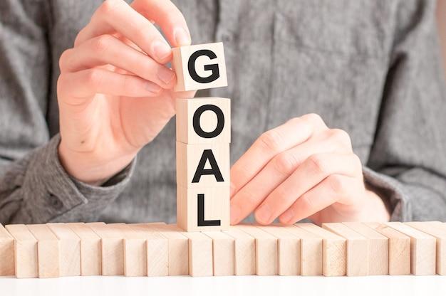Рука кладет деревянный куб с буквой g от слова цель. слово написано на деревянных кубиках, стоящих на белой поверхности стола.