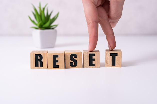 手は、リセットという単語の文字rが付いた木製の立方体を置きます。言葉はテーブルの黄色い表面に立っている木製の立方体に書かれています。