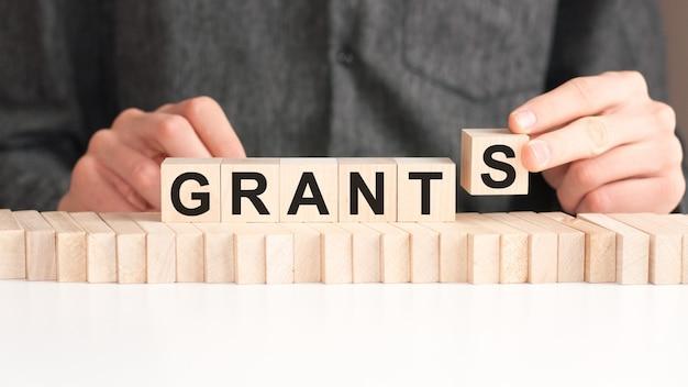 손은 grants라는 단어에서 문자 s가있는 나무 큐브를 놓습니다. 단어는 테이블의 흰색 표면에 서있는 나무 큐브에 기록됩니다.