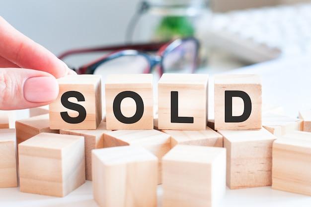 Рука кладет деревянный куб с буквой s от слова sold.