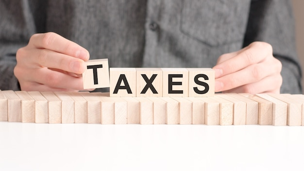 손은 taxes라는 단어에서 문자 t가있는 나무 큐브를 놓습니다.