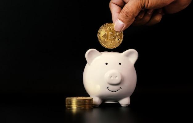 Рука, вкладывающая биткойн в копилку, риск и богатство могут случиться при торговле криптовалютой