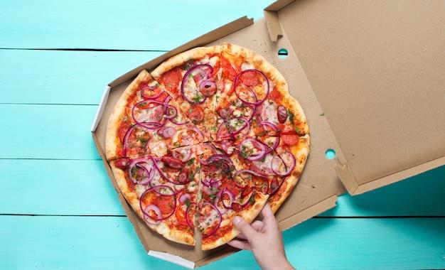 手は、青いコンクリートのテーブルのボックスにピザの切れ端を取ります。上面図