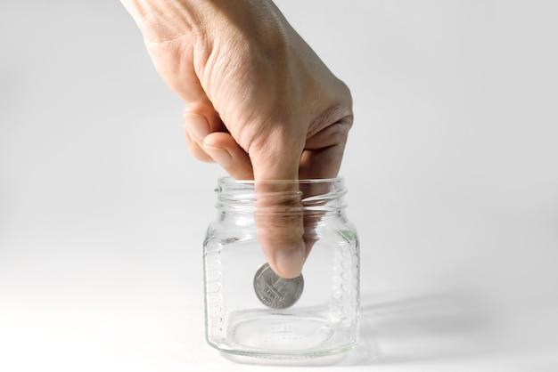 手はガラスから最後のコインを取ります、クローズアップ。