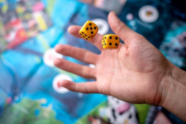 손은 경기장에 두 개의 노란 주사위를 던졌습니다. 보드 게임의 개념. 역동적 인 게임 순간