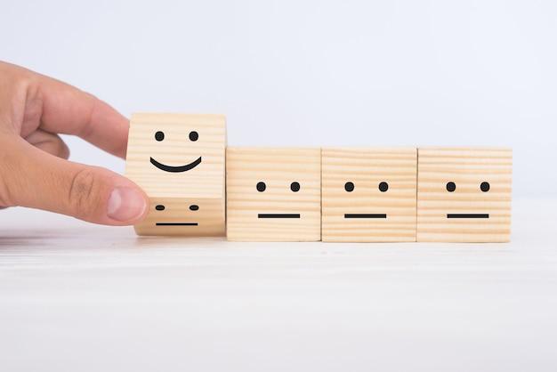 손은 슬픈 사람들 사이에서 웃는 웃는 얼굴로 큐브를 돌립니다. 최고의 비즈니스 서비스, 고객 서비스 평가, 만족도 조사 개념.
