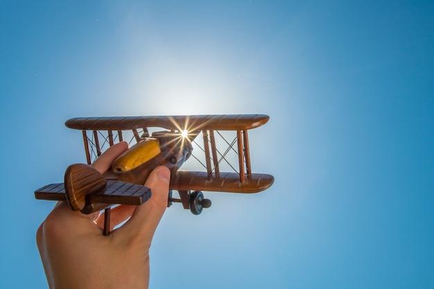 澄んだ空を背景におもちゃの飛行機を持った手