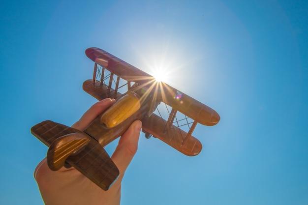太陽の背景に木製の鉋を持つ手