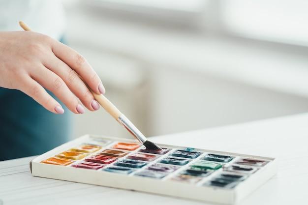 ブラシと絵の具で作業する手