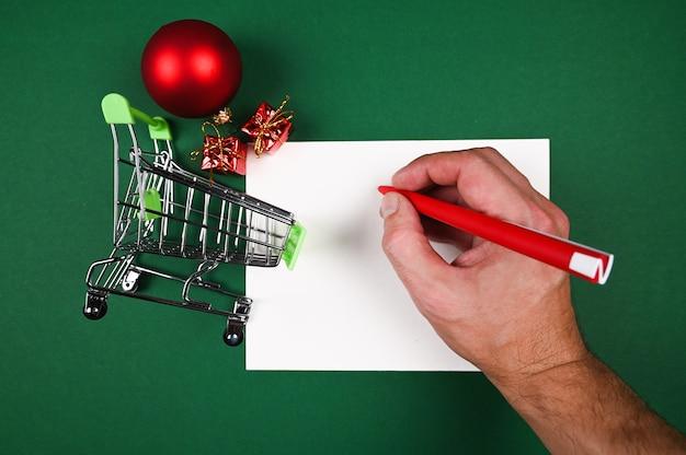 Рука пишет заметки о покупке новогодних подарков.