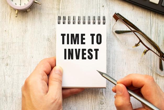 손은 노트북에 연필로 time to invest 텍스트를 씁니다. 위에서 봅니다. 비즈니스 개념.
