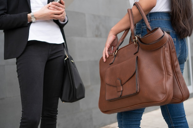 직장에서 대화하는 두 경제인의 손과 가방.