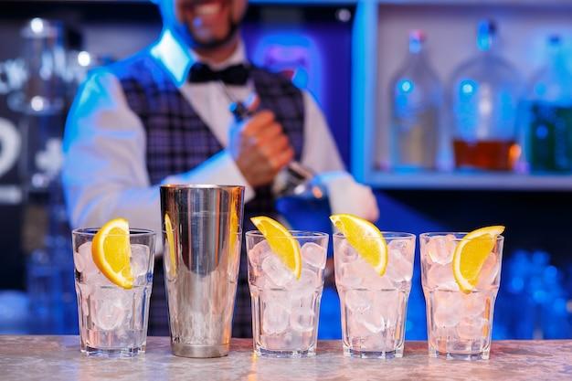 仕事中のバーマンの手のクローズアップ、彼はカクテルを準備しています。サービスと飲み物についての概念。