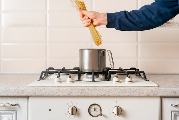 В руках держите пучок сырых спагетти и готовьте его. итальянская паста с лапшой традиционная