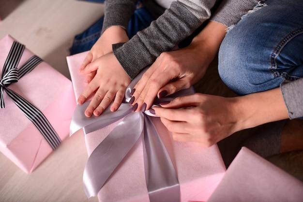 プレゼントボックスを開梱しようとしている手の母と娘