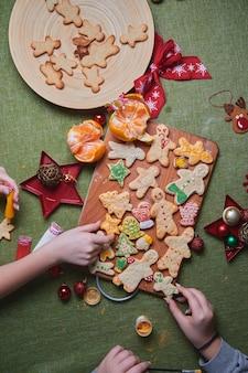 구운 된 생강 남자를 들고 아름 다운 젊은 여자의 손. 집안의 만찬, 가족 저녁 식사의 개념. 새해 전통 개념과 요리 과정. 가족 만들기