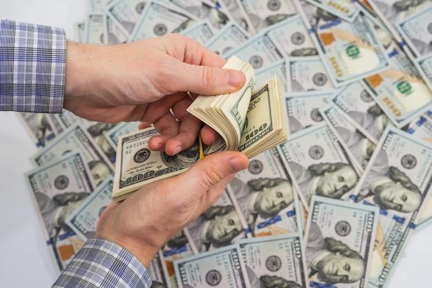 ビジネスマンの手はドルを数えています。富の概念。