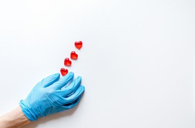 ハートの形で石を保持している白い表面上の医療用手袋の医師の手