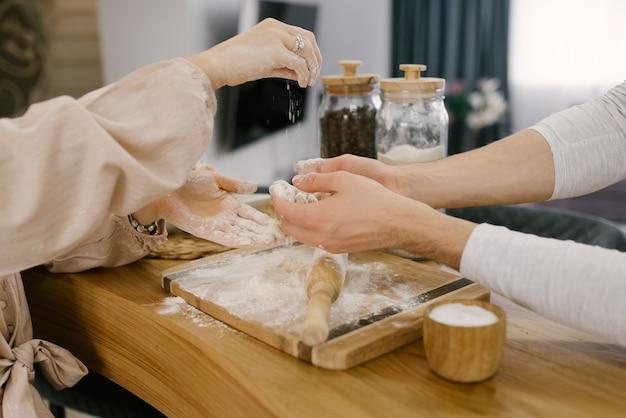 男と女の手が木製のテーブルに麺棒で生地と小麦粉を準備しています。セレクティブフォーカス