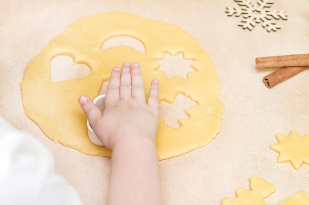 어린 소녀의 손이 과자 쿠키를 만듭니다. 크리스마스 베이킹