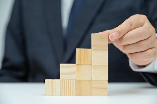 나무 블록을 쌓고 있는 남성 사업가의 손. 비즈니스 개념입니다.