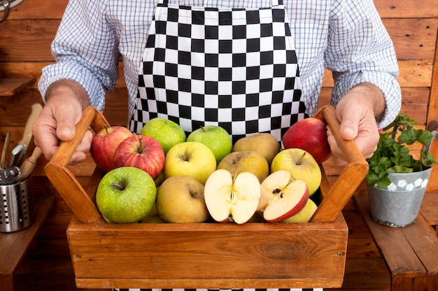 한 남자의 손은 다양한 품질과 색상의 사과로 가득 찬 바구니를 들고 있습니다. 배경과 소박한 나무 테이블입니다. 시니어 성인 1명