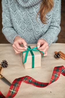 Руки молодой женщины создают и упаковывают рождественские и новогодние подарки к празднику. подарки и поздравления. бинты с зеленой лентой. по горизонтали