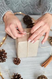 Руки молодой женщины создают и упаковывают рождественские и новогодние подарки к празднику. подарки родным и близким с поздравлением